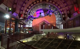 Plane hanging from the roof of museum with purple lighting